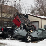 Car winds up on top of parked vehicles outside Minneapolis home